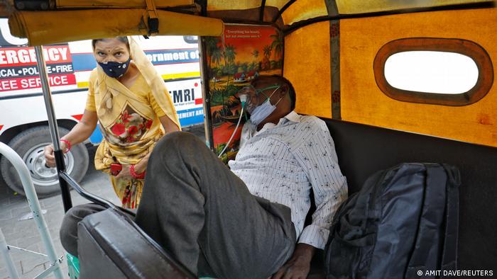 بسیاری بیماران در شفاخانه جای نمییابند و ساعتها پیش روی شفاخانه انتظار میکشند، مانند این مرد در داخل یک ریکشا در شهر احمد آباد. او خوشبخت است که حداقل یک کپسول اکسیجن دریافت کرده است. مقامها گفته اند که تنها در دهلی دست کم به ۵۰۰۰ بستر مراقبت عاجل نیاز است و بسیاری شفاخانهها با کمبود اکسیجن مواجه اند.