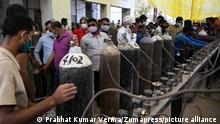 People wait at a distribution center for oxygen cylinders