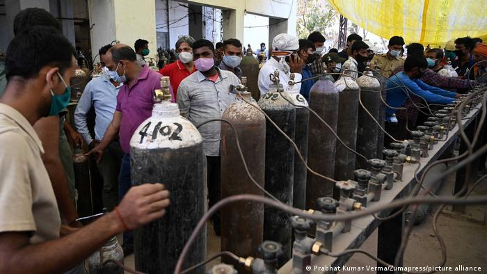 در بسیاری مناطق این کشور، مانند اینجا در شهر االله آباد، مردم به مراکز فروش اکسیجن مراجعه میکنند تا کپسولهای اکسیجن را برای اقارب خود برسانند. قیمت آکسیجن نیز در بازار سیاه بسیار بالا رفته است. حکومت در نظر دارد دستگاههای صنعتی را که آکسیجن مصرف میکنند تعطیل کند تا به مریضان آکسیجن رسانده شود.