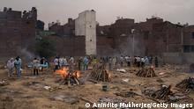 """*** Dieses Bild ist fertig zugeschnitten als Social Media Snack (für Facebook, Twitter, Instagram) im Tableau zu finden: Fach """"Images"""" *** NEW DELHI, INDIA - APRIL 20: Multiple funeral pyres of those patients who died of the Covid-19 coronavirus disease are seen burning at a ground converted into a makeshift crematorium where mass cremation of covid deaths were held on April 20, 2021 in New Delhi, India. Covid-19 cases are spiralling out of control in India, with daily infections approaching 300,000, according to health ministry data, bringing the nationwide tally of infections to almost 14 million. The latest wave has already overwhelmed hospitals and crematoriums. (Photo by Anindito Mukherjee/Getty Images)"""