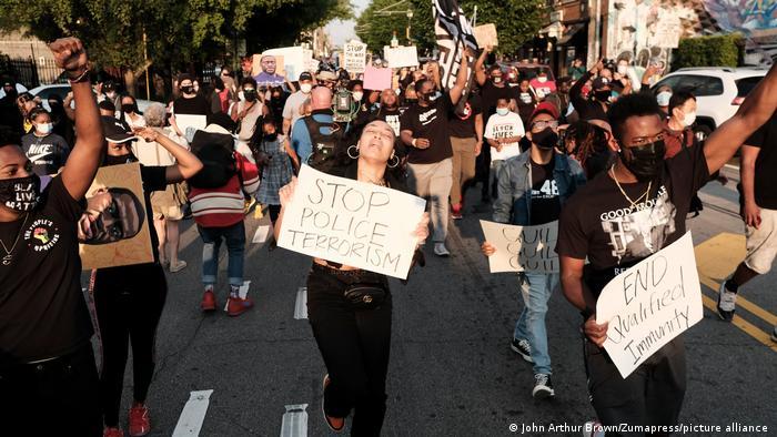 Manifestante segura cartaz com os dizeres Pare com o terrorismo policial enquanto marcha pelo centro de Atlanta, nos EUA, em homenagem a George Floyd no dia 20 de abril de 2021, mesmo dia em que o ex-policial de Minneapolis Derek Chauvin foi considerado culpado de três acusações de assassinato por seu papel na morte de Floyd.