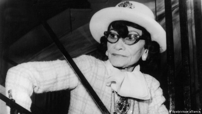 Coco Chanel wearing a white suit and dark-rimmed glasses and a white hat.