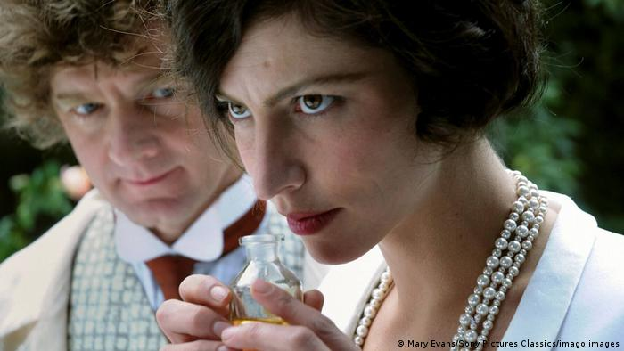 Film stil from Coco Chanel showing actress Anna Mouglalis smelling the scent from a perfume bottle. A male actor stands behind her.