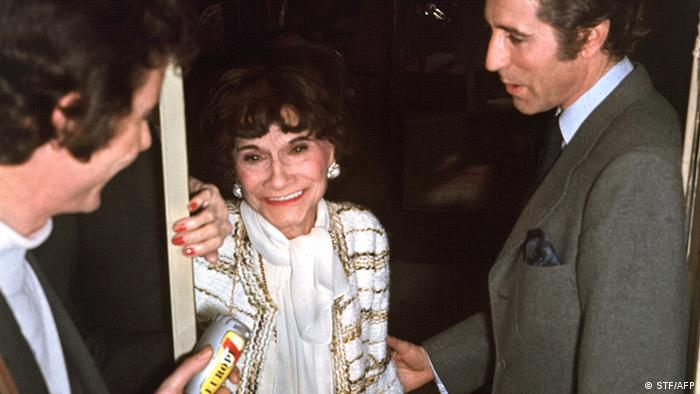 French fashion designer Coco Chanel, smiling, as she is congratulated by French principal dancer Jacques Chazot in 1958.