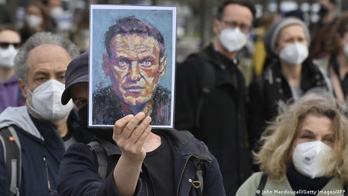 Участник митинга в поддержку Навального держит в поднятой руке его портрет