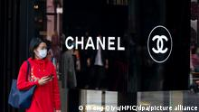 People walk past a Chanel store in Beijing, China, 6 April 2020.