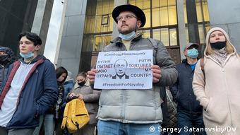 Протестующие в Москве, молодой челрвек с плакатом Свободу Навальному