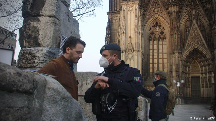 Ben, left, being spoken to by local police in front of Cologne Cathedral