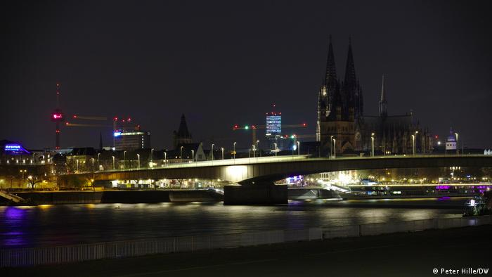 During curfew, the normally illuminated Cologne Cathedral remains dark