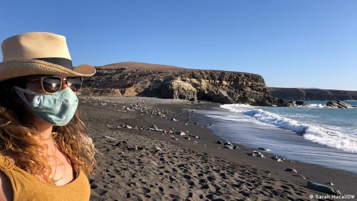 Una mujer con gafas de sol y una máscara se encuentra junto al mar en una playa de la isla de Fuerteventura.