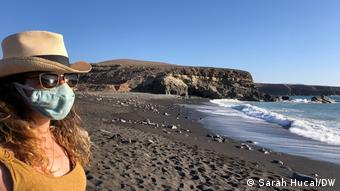 Девушка в защитной маске смотрит на пустующие пляжи на Канарских островах в Испании, 2021 год