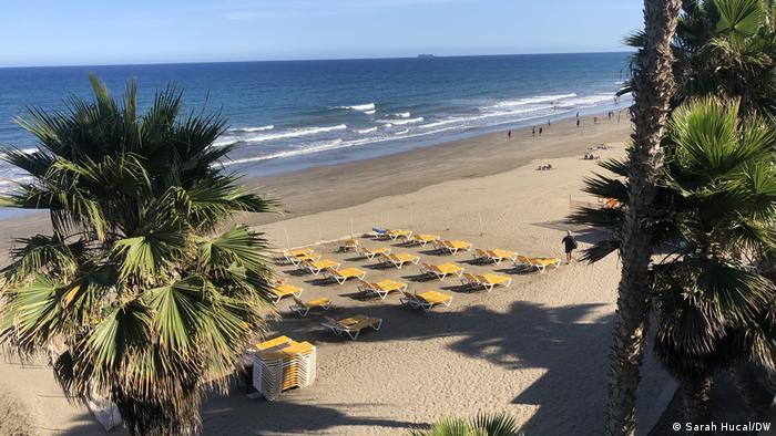 Sillas de playa en blanco en la playa junto a palmeras en Playa del Inks en Gran Canaria