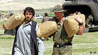 An Afghan man and a German peacekeeper, right, carry international aid