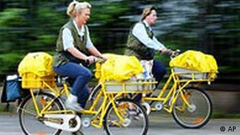 Two mail carriers on bikes with yellow bags