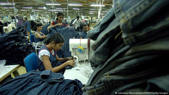 Young women sew jeans in a factory
