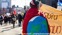 An environmental demonstrator is viewed from behind, marching on a crowded street with during a demonstration against climate change
