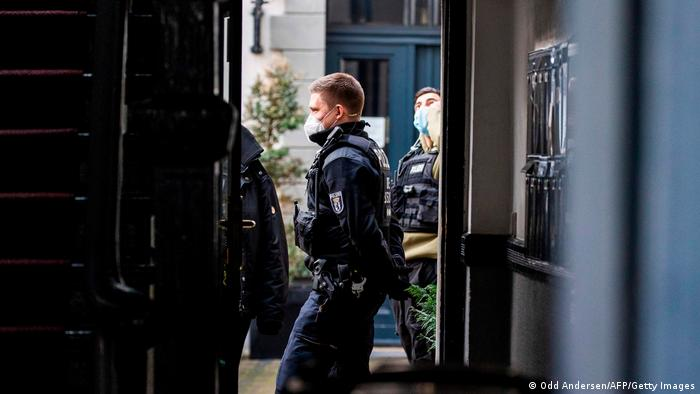 A police officer standing in the door frame of a building in Berlin