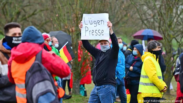 A man holding a 'Lügenpresse' sign at a protest