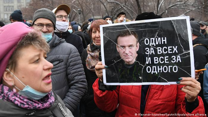 Demonstranten, einer mit einem Nawalny-Plakat