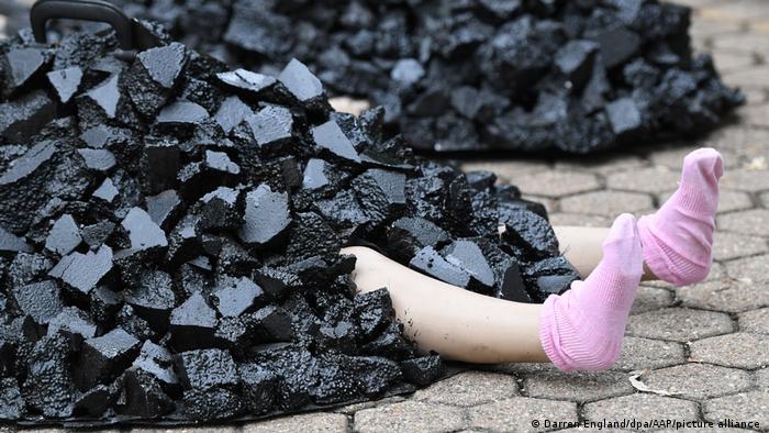 """Lutka ispod gomile uglja: aktivisti """"Extinction Rebellion"""" iz Australije tim performansom žele da upozore na zagađenje koje prouzrokuje upotreba tog energenta."""