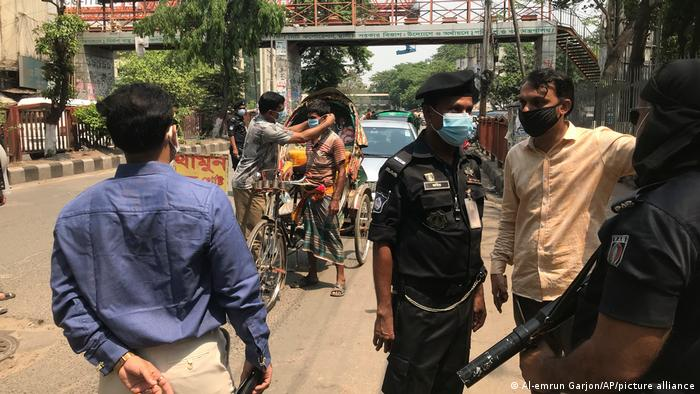 Bangladeshi police make a rickshaw puller wear a mask as they enforce a lockdown in Dhaka