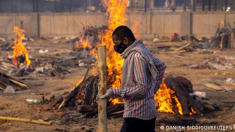 A man walks past burning funeral pyres of people, who died of COVID-19 at a crematorium ground in New Delhi