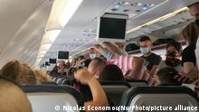 Passengers with facemasks boarding inside an Aegean Airbus A320. Flying in an Aegean Airlines Airbus A320 during the Coronavirus pandemic era with obligatory usage of face masks for the passengers in the plane and the airport. The flight crew, female air stewardess are wearing also safety equipment such as facemasks and gloves while the meals are changed and a disinfecting napkin is provided. The domestic flight route is from Thessaloniki SKG LGTS to Athens ATH LGAV Airport, the Greek capital. The Greek Government lifted the traffic ban, lockdown quarantine measures for tourists, easing generally the measures to relaunch the tourism season, with more Covid tests at the airports and the entry points to Greece on Jule 1, 2020. Although there are still some countries whose citizens are banned due to the increased numbers of Coronavirus cases. Covid-19 cases skyrocket in Greece the past few days as tourists and locals are more relaxed without keeping the social distancing and mandatory safety measures such as protective mask during their summer holidays in tourist destinations so Greece records massive coronavirus spike. Every day the greek government implements new protective measures like reducing the number of people in events, changing the working hours for bars and restaurants or obligatory usage of facemask in specific places. in Athens, Greece, on August, 13, 2020. (Photo by Nicolas Economou/NurPhoto)