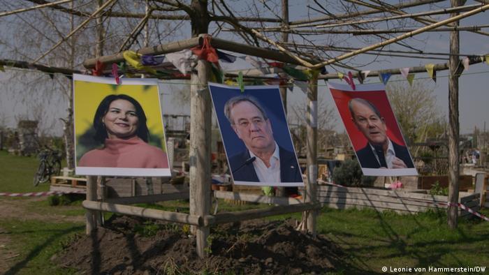 Photos of Annalena Baerbock, Armin Laschet and Olaf Scholz hang on a washing line