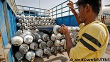 22.04.21 *** A worker loads empty oxygen cylinders onto a supply van to be transported to a filling station, at a COVID-19 hospital, amidst the spread of the coronavirus disease (COVID-19) in Ahmedabad, India, April 22, 2021. REUTERS/Amit Dave