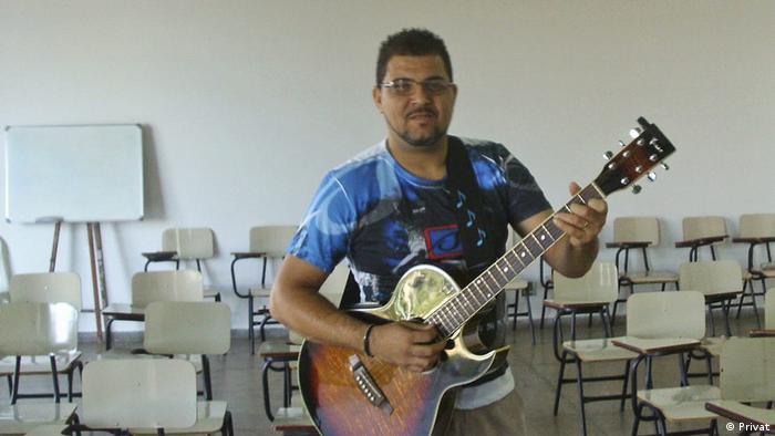 Homem toca guitarra em sala cheia de cadeiras