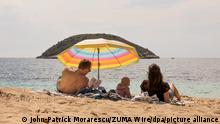 A family on a beach under a parasol looking out at the sea, Spain