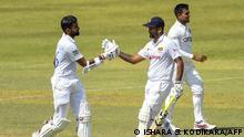 Sri Lanka's Lahiru Thirimanne (L) celebrates after scoring a half-century (50 runs) with teammate Sri Lanka's Dimuth Karunaratne during the third day of the first Test cricket match between Sri Lanka and Bangladesh at the Pallekele International Cricket Stadium in Kandy on April 23, 2021. (Photo by Ishara S. KODIKARA / AFP)