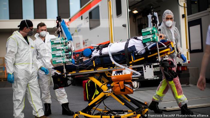 Foto mostra paciente sendo transportado em uma maca, com muitos aparelhos. Três profissionais auxiliam na locomoção. Todos usam máscara de proteção.