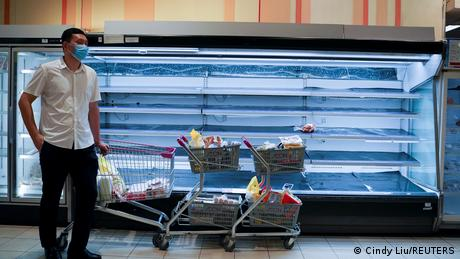 A man wearing a protective face mask stands next to an empty shelf at a market in Phnom Penh