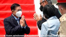 In this photo released by Indonesian Presidential Palace, Myanmar's Senior General Min Aung Hlaing, left, is greeted by an unidentified Indonesian officials upon arrival at Soekarno-Hatta International Airport in Tangerang on the outskirts of Jakarta, Indonesia, Saturday, April 24, 2021. Southeast Asian leaders are to meet Myanmar's top general and coup leader in an emergency summit in Indonesia Saturday, and are expected to press calls for an end to violence by security forces that has left hundreds of protesters dead as well as the release of Aung San Suu Kyi and other political detainees. (Rusman/Indonesian Presidential Palace via AP)