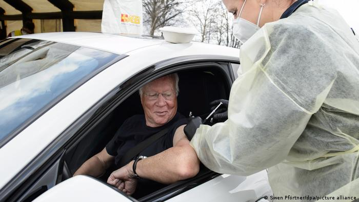 A man being vaccinated in his car