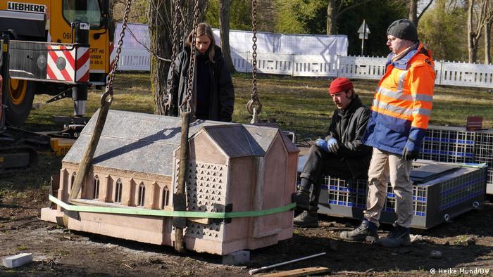 Lastkran platziert eine Miniatur-Kirche aus Beton auf erdigem Boden, Drei Männer stehen daneben.