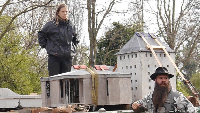 Die Künstler Marta Dyachenko und Julius von Bismarck blicken auf die Landschaft, zwischen ihnen stehen Haus-Skulpturen aus Beton.
