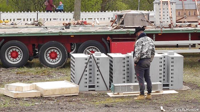 Mann steht vor einer Skulptur, die ein etwa kniehohes Mietshaus zeigt. Dahinter ist ein entladener LKW zu sehen.