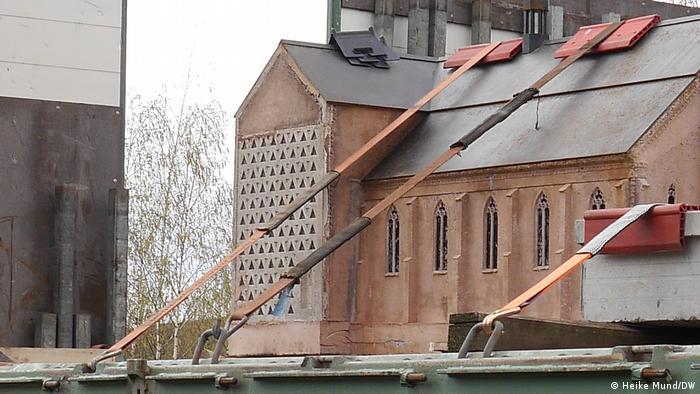Eine Kirchengebäude in Miniaturformat steht fest vertäut auf einem LKW.