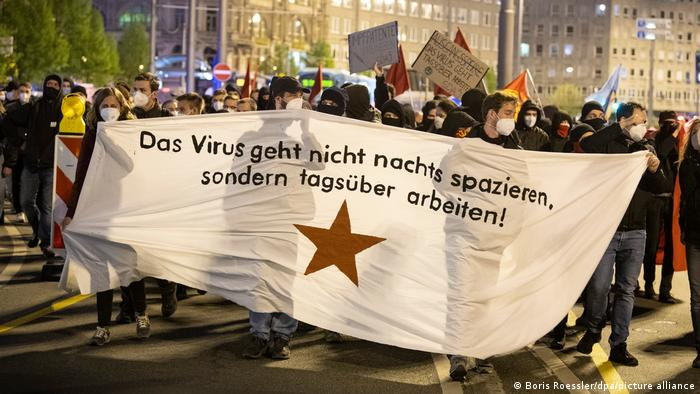 Protesters in Frankfurt hold a banner reading: 'The virus doesn't walk at night, it works during the day'