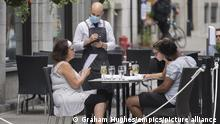 server wears a face mask as he takes an order at an outdoor terrace in Montreal