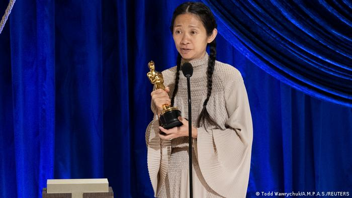 Chloe Zhao holds her Oscar for best director.