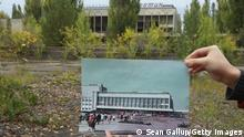 """*** Dieses Bild ist fertig zugeschnitten als Social Media Snack (für Facebook, Twitter, Instagram) im Tableau zu finden: Fach """"Images"""" *** PRIPYAT, UKRAINE - SEPTEMBER 29: An assistant holds up a photo showing the city of Pripyat's main square and the Energetik cultural center before 1986 at the same site that today is abandoned and overgrown with trees on September 29, 2015 in Pripyat, Ukraine. Pripyat lies only a few kilometers from the former Chernobyl nuclear power plant and was built in the 1970s to house the plant's workers and their families. On April 26, 1986, technicians at Chernobyl conducting a test inadvertently caused reactor number four to explode, sending plumes of highly radioactive particles and debris into the atmosphere. Authorities evacuated 120,000 people from the area, including 43,000 from Pripyat. Today Pripyat is a ghost-town, its apartment buildings, shops, restaurants, hospital, schools, cultural center and sports facilities derelict and its streets overgrown with trees. The city lies in the inner exclusion zone around Chernobyl where hot spots of persistently high levels of radiation make the area uninhabitable for thousands of years to come. (Photo by Sean Gallup/Getty Images)"""