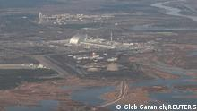 An aerial view from a plane shows a New Safe Confinement (NSC) structure over the old sarcophagus covering the damaged fourth reactor at the Chernobyl Nuclear Power Plant during a tour to the Chernobyl exclusion zone, Ukraine April 3, 2021. Ukraine International Airlines made a special offer marking the 35th anniversary of the Chernobyl nuclear disaster. Tourists get a bird's eye view of abandoned buildings in the ghost town of Pripyat and the massive domed structure covering a reactor of the Chernobyl Nuclear Power Plant that exploded on April 26, 1986. Picture taken April 3, 2021. REUTERS/Gleb Garanich