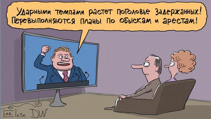 Мужчина и женщина сидят на диване и смотрят пропагандистскую программу по ТВ