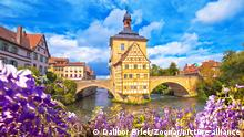 Scenic view of Old Town Hall of Bamberg (Altes Rathaus) with two bridges over the Regnitz river flower view, Upper Franconia, Bavaria region of Germany