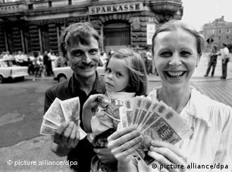 A family holding up their new deutschmarks