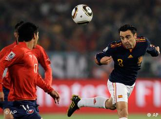 Spain's Xavi Hernandez heads the ball in the match against Chile