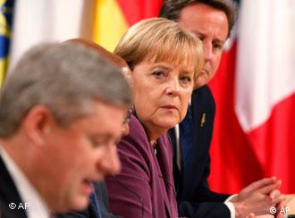 German Chancellor Angela Merkel and British Prime Minister David Cameron listen as Canadian Prime Minister Stephen Harper speaks